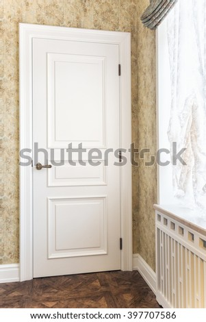 The white closed door near a window.