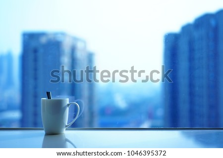 The white coffee cup is on the windowsill and the background is a hazy cityscape.