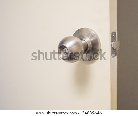 The white door with metal doorknob is regular lock style in modern house - stock photo