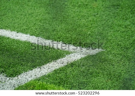 The white grass line at green grass football field.