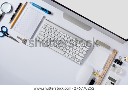 The white office table with stationery accessories, keyboard,computer mouse and notepad. Top view.