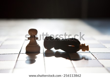 the White Pawn beat black chess king on board background - stock photo