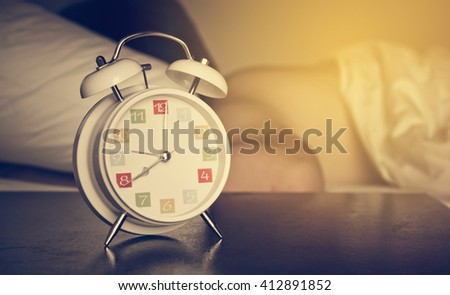 The white retro alarm clock with colorful number is showing 8 o'clock and a man lying on bed in out of focus background.  Vintage style and filtered process. - stock photo