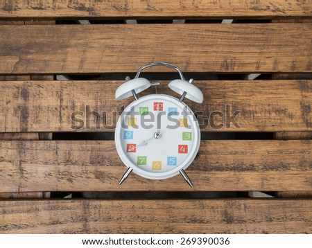 The  white retro alarm clock with colorful number is showing 8 o'clock on wooden background - stock photo