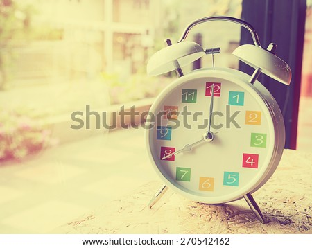 The  white retro alarm clock with colorful number is showing 8 o'clock on wooden background and window glass in vintage style. - stock photo