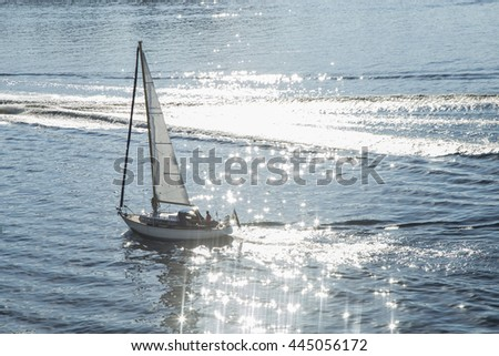 The white sail of yacht on the background of sea. Beautiful sunlight in the water.