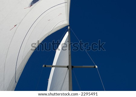The white sails of a sailboat. - stock photo