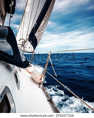 The white sails of yachts on the background of sea and sky in the clouds - stock photo
