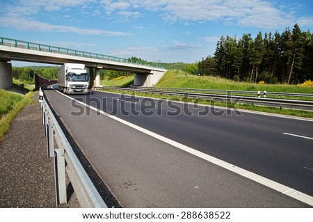 The white truck rides under a concrete bridge over a highway in a wooded landscape. Noise protection wall. White clouds in the blue sky. - stock photo