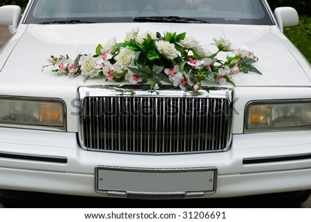 The white wedding car decorated with flowers - stock photo
