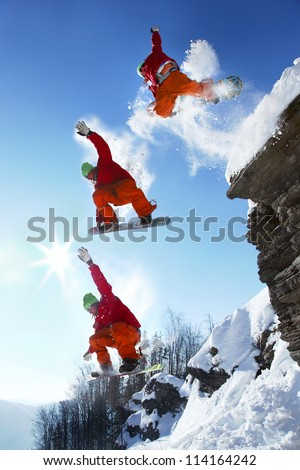 The whole jump of Snowboarder from high cliff in mountains - stock photo