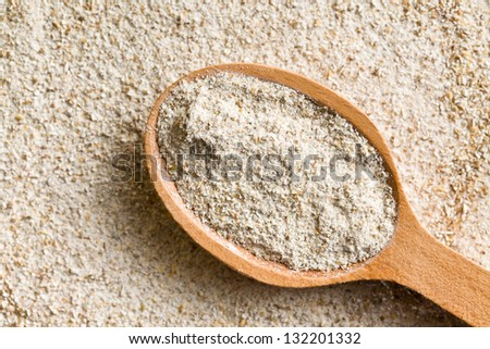 the wholemeal flour in wooden spoon - stock photo