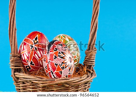 The wicker basket and Easter painted eggs .