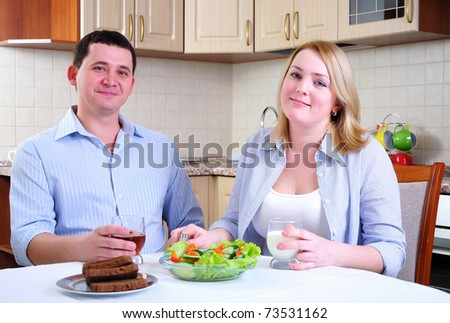 The wife and husband have breakfast together in his kitchen.