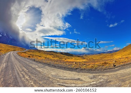 The wind begins. Sunset in the Chilean Patagonia. The gravel road among hills of national park to Torres del Paine - stock photo