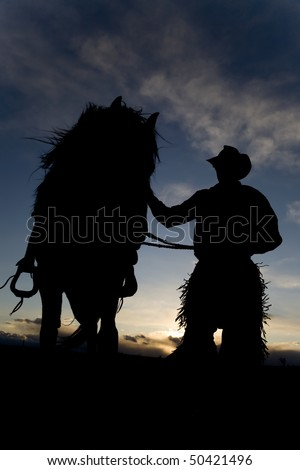 The wind blowing the main of a horse that a cowboy holds - stock photo