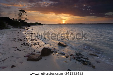 The wind in your hair and the waves lapping your feet.  A glorious summer sunset over Botany Bay, Sydney, Australia - stock photo