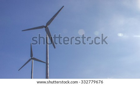 The wind turbine on the blue sky