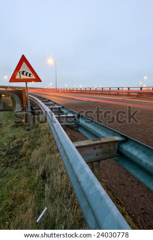 The wind vane on a sign, warning the traffic for heavy winds on the motorway overpass - stock photo