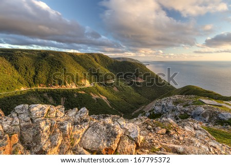 The winding Cabot Trail road seen from high above on the Skyline Trail at sunset in Cape Breton Highlands National Park, Nova Scotia - stock photo