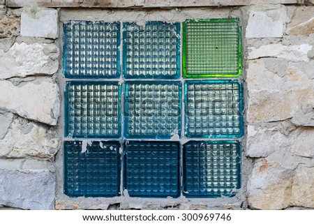 The window from opaque blue glass blocks in the wall of an abandoned old stone house - stock photo