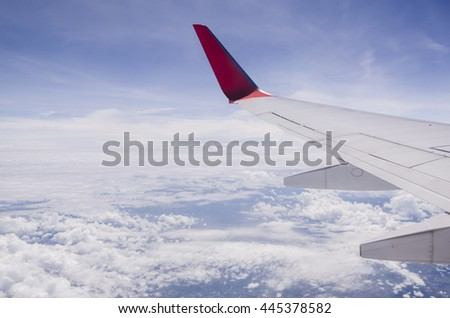 The wing of a plane flying over the sky