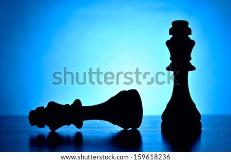 The winner and the loser depicted by two chess pieces with the victorious king standing upright over his fallen competition or foe silhouetted against a graduated blue background with copyspace - stock photo