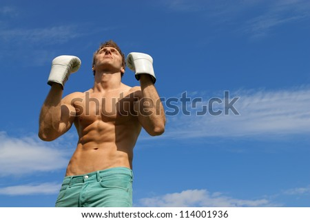 The winner. Strong man in boxing gloves on blue sky background.