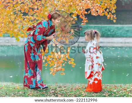 The woman and girl dressed in Japanese kimono walk in autumn park - stock photo