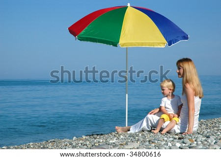 The woman and the child under an umbrella look at the sea