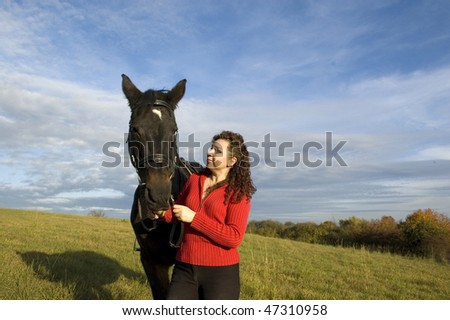 The woman and the horse are on the field on a  background of the cloudy sky.