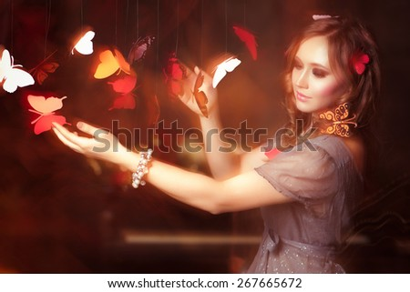 The woman catches butterflies. Some butterflies sit on in her hair - stock photo