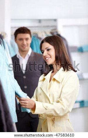 The woman chooses clothes on a forward background