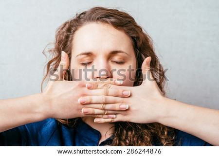 The woman closed her hands over her mouth. Gray background - stock photo