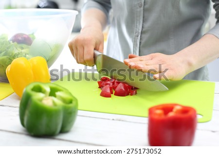 The woman cuts pepper for salad. Woman hands while cutting peppers