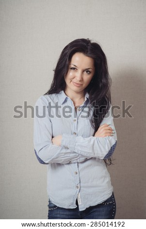 The woman folded her arms . On a gray background.