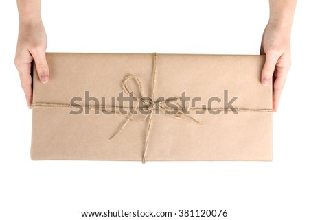 the woman holds in her hands a beautiful and great gift that is bound  rope on white background isolated - stock photo