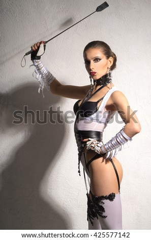 The woman in a beautiful ladies' fetish lingerie stands with a whip - stock photo