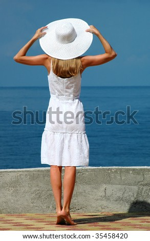 The woman in a white hat with the lifted hands - stock photo