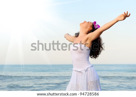 The woman in a white sundress on seacoast with open hands. Sun light
