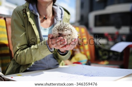The woman in an autumn jacket sits at a table and holds a little hedgehog in hand - stock photo