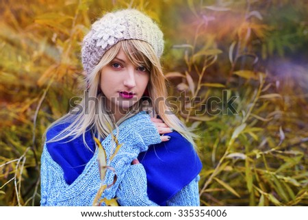 The woman in autumn knitted clothes poses on the island, an autumn depression - stock photo