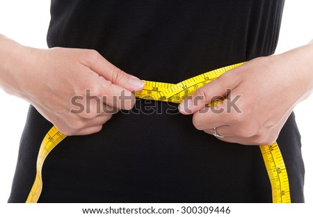 The woman in black measures her waist circumference with measuring tape on white background. - stock photo