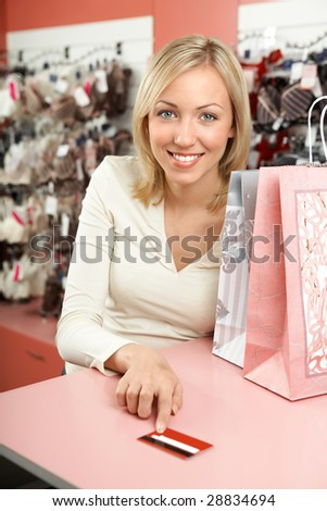 The woman in shop with packages smiles and holds in a hand a credit card - stock photo