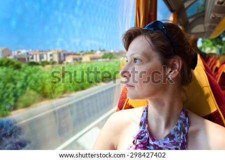 The woman in the bus looks out of the window