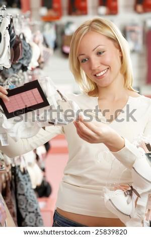 The woman in underwear shop considers a brassiere - stock photo