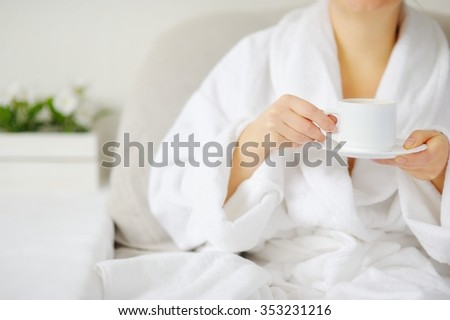 The woman in white bathrobe at the table drinking a hot drink