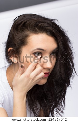 the woman inserts contact lenses - stock photo