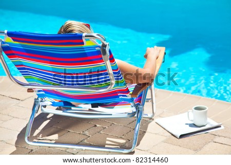 The woman is sitting near the pool - stock photo