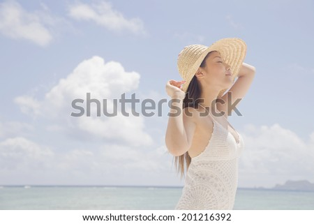 The woman looks up at the sky while holding a brim of a straw hat - stock photo